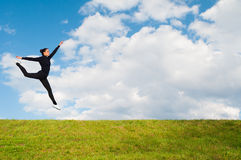 Young happy ballerina jumping high in the air over meadow agains Stock Image