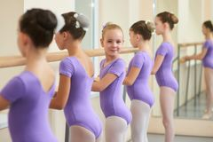 Young happy ballerina near ballet barre. Cute little ballet dancers practicing some dance element at a barre in a dance class. Professional school of ballet royalty free stock images