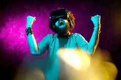 Young happy bearded hipster man with curly hair wearing virtual reality goggles in studio in neon lights. Smartphone. Using with VR headset. Winner concept royalty free stock image