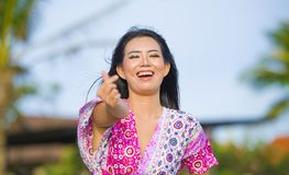 Young happy beautiful Asian Chinese tourist woman doing love sign with fingers and hand posing and laughing at beach tropical reso. Rt on holidays trip enjoying Stock Photo