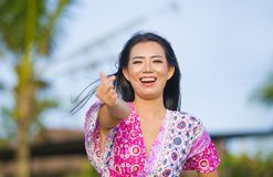 Young happy beautiful Asian Chinese tourist woman doing love sign with fingers and hand posing and laughing at beach tropical reso. Rt on holidays trip enjoying Royalty Free Stock Photos