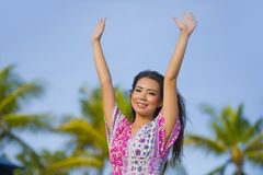 Young happy beautiful Asian Chinese tourist woman smiling relaxed wearing sweet dress walking rising arms free at tropical resort. Young happy beautiful Asian Royalty Free Stock Photography