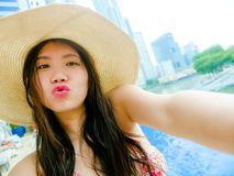 Young happy and beautiful Asian Chinese tourist woman taking selfie picture with mobile phone camera at luxury hotel infinity poo royalty free stock photo