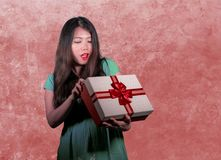 Young happy and beautiful Asian Chinese woman holding gift box receiving birthday or Christmas present opening the parcel excited Stock Photo