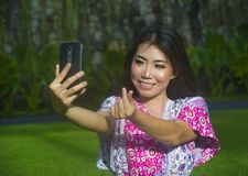 Young happy and beautiful Asian Chinese woman taking selfie pic with mobile phone camera doing love sign with hand fingers outdoor. S on green grass park in Royalty Free Stock Images