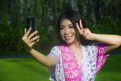 Young happy and beautiful Asian Chinese woman taking selfie pic with mobile phone camera doing peace sign with hand fingers outdoo. Rs on green grass park in Stock Photo