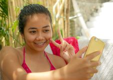 Young happy and beautiful Asian Indonesian teenager girl in bikini sitting on pool bed with sarong taking selfie picture with royalty free stock photography
