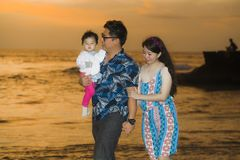 Young happy and beautiful Asian Korean couple holding baby girl daughter walking on sunset beach enjoying together romantic summer royalty free stock images