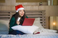 Young happy and beautiful Asian Korean girl on bed in Santa Christmas hat using credit card and laptop computer for online shoppin