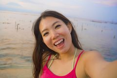 Young happy and beautiful Asian Korean tourist woman taking self portrait selfie with mobile phone smiling having fun at sunset be royalty free stock photo
