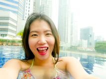 Young happy and beautiful Asian Korean tourist woman taking selfie picture with mobile phone camera at luxury hotel infinity pool. With modern buildings urban royalty free stock image