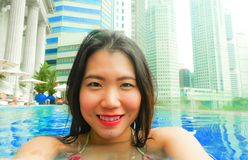 Young happy and beautiful Asian Korean tourist woman taking selfie picture with mobile phone camera at luxury hotel infinity pool. With modern buildings urban stock image