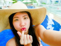 Young happy and beautiful Asian Korean tourist woman taking selfie picture with mobile phone camera at luxury hotel infinity pool. With modern buildings urban royalty free stock photography