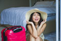 Young happy and beautiful Asian Korean tourist woman with travel suitcase arriving at hotel sitting on room floor excited and play. Lifestyle natural portrait of royalty free stock images
