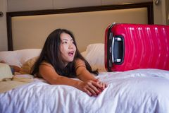 Young happy and beautiful Asian Korean tourist woman with travel suitcase just arrived at five star hotel room playing on bed. Lifestyle portrait of young happy royalty free stock images