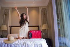 Young happy and beautiful Asian Korean tourist woman with travel suitcase just arrived at five star hotel room playing on bed. Lifestyle portrait of young happy stock images