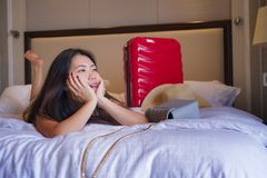 Young happy and beautiful Asian Korean tourist woman with travel suitcase just arrived at five star hotel room playing on bed. Lifestyle portrait of young happy stock photo