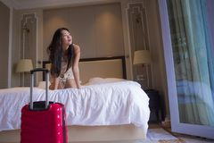 Young happy and beautiful Asian Korean tourist woman with travel suitcase just arrived at five star hotel room playing on bed. Lifestyle portrait of young happy royalty free stock image