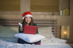 Young happy and beautiful Asian Korean woman on bed in Santa Christmas hat using credit card and laptop computer for online shoppi stock image