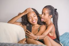 Young happy and beautiful Asian sisters or girlfriends couple sm. Iling cheerful taking selfie photo with mobile phone at home couch playful laughing together in stock photos