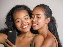 Young happy and beautiful Asian sisters or girlfriends couple smiling cheerful taking selfie photo with mobile phone at home stock photo