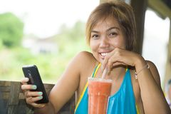 Young happy beautiful Asian woman in coffee shop using internet app on mobile phone drinking healthy fruit juice with a straw Royalty Free Stock Images