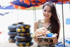 Young happy beautiful Asian woman smiling while holding plate of royalty free stock image