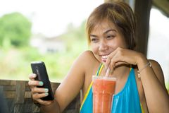 Young happy beautiful Asian woman in coffee shop using internet app on mobile phone drinking healthy fruit juice with a straw Stock Photography
