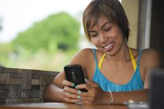 Young happy beautiful and attractive Asian woman sitting in coffee shop using internet app on mobile phone smiling relaxed outdoor Stock Images