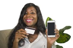 Young happy and beautiful black African American woman at home couch using credit card for buying and banking online with mobile p royalty free stock photography