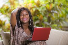 Young happy and beautiful black afro American woman in fashionable dress and working with laptop computer enjoying freelance stock photography
