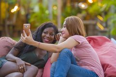 Young happy and beautiful black afro American woman enjoying holidays at tropical resort with Asian girlfriend taking selfie. Young happy and beautiful black royalty free stock photo