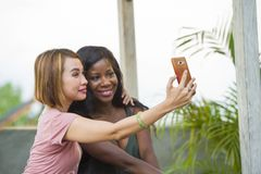 Young happy and beautiful black afro American woman enjoying holidays at tropical resort with Asian girlfriend taking selfie. Young happy and beautiful black stock photo
