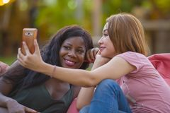 Young happy and beautiful black afro American woman enjoying holidays at tropical resort with Asian girlfriend taking selfie stock photos