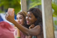 Young happy and beautiful black afro American woman enjoying holidays at tropical resort with Asian girlfriend taking selfie. Young happy and beautiful black stock images