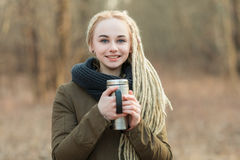 Young happy beautiful blonde hipster woman posing with thermos cup cold season outdoors Stock Photo