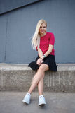 Young happy beautiful blonde woman sitting on the concrete river pier and looking into camera Stock Image