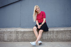 Young happy beautiful blonde woman sitting on the concrete river pier and looking into camera Stock Photos