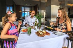 Young happy beautiful Caucasian family of father, mother and daughter have dinner by served restaurant table together royalty free stock photos
