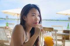 Young happy and beautiful Chinese Asian woman drinking healthy orange juice sitting at beach restaurant resort enjoying Summer hol. Iday vacation trip to Stock Image
