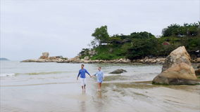 Young happy beautiful couple of lovers, in blue clothes, holding hands, walking along the seashore, talking and smileing stock video footage