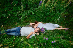 Young happy beautiful couple man and woman lying outdoors on green grass Stock Photos