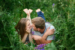 Young happy beautiful couple man and woman lying outdoors on green grass Stock Photography