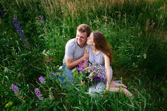 Young happy beautiful couple sitting in green meadow Stock Image