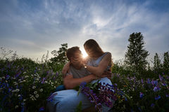 Young happy beautiful couple sitting in green meadow Royalty Free Stock Photos