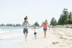 Young happy and beautiful family mother father holding hand of son and daughter walking joyful on the beach enjoying Summer holida royalty free stock image