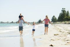 Young happy and beautiful family mother father holding hand of son and daughter walking joyful on the beach enjoying Summer holida royalty free stock images
