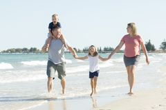 Young happy and beautiful family mother father holding hand of son and daughter walking joyful on the beach enjoying Summer holida royalty free stock photo