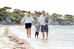 Young happy beautiful family walking together on the beach enjoying summer holidays Stock Images