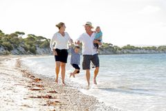 Young happy beautiful family walking together on the beach enjoying summer holidays Royalty Free Stock Photo
